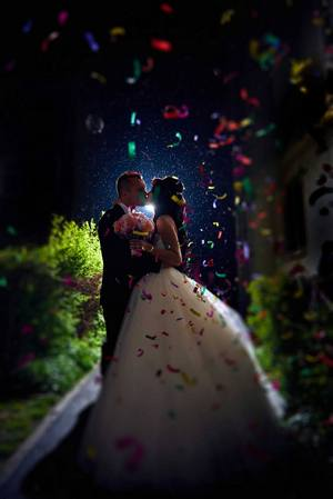 Beautiful confetti shower for a newlywed couple sharing a kiss.
