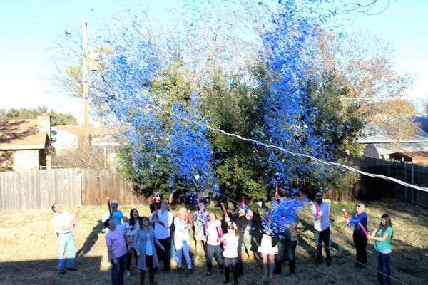 Big party with everyone shooting blue confetti for a boy's gender reveal party.
