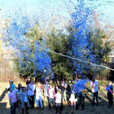 Gender reveal confetti cannons blasting blue confetti high into the air. It's a boy.