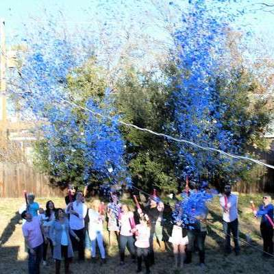 Blue confetti blasting out from a bunch of gender reveal confetti cannons for a boy.