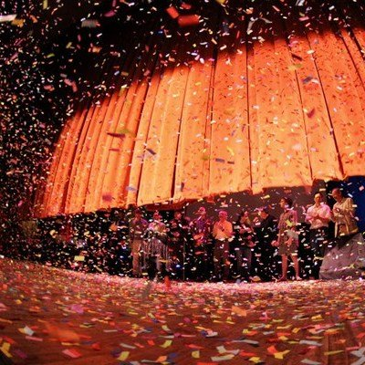 The grand finale with colorful confetti  shooting onto the stage while the curtain is coming down.