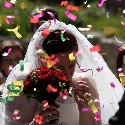 Beautiful and colorful tissue confetti is slowly falling all around the bride making a picture perfect moment.